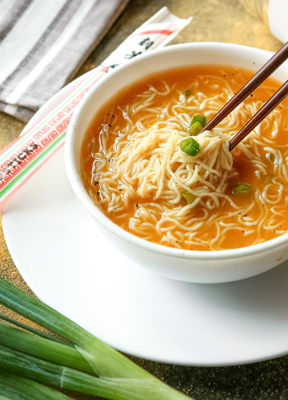 Ramen soup in a bowl with chopsticks removing noodles.