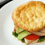Carb free cloud bread being used as the bread for a turkey avocado and tomato sandwich.