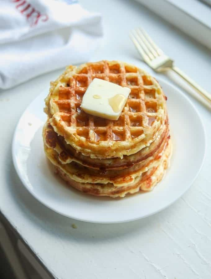 A white plate with a stack of chaffles topped with butter and syrup on it.