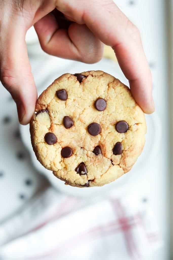 A chocolate chip cookie being held between 2 fingers.