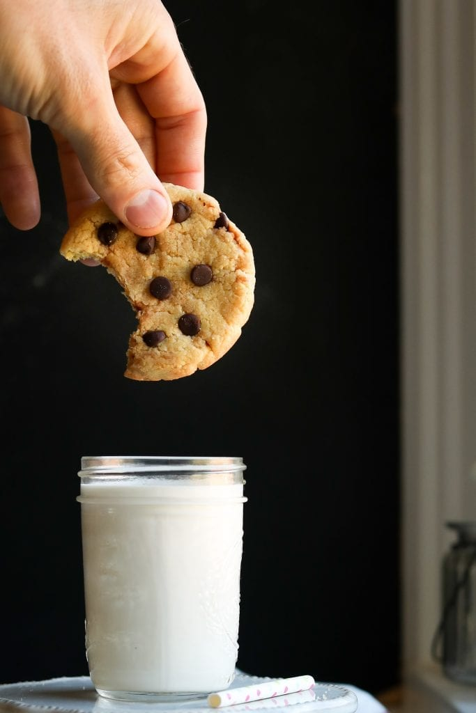 A chocolate chip cooking with a bite taken out of it, about to be dunked into a glass of milk.