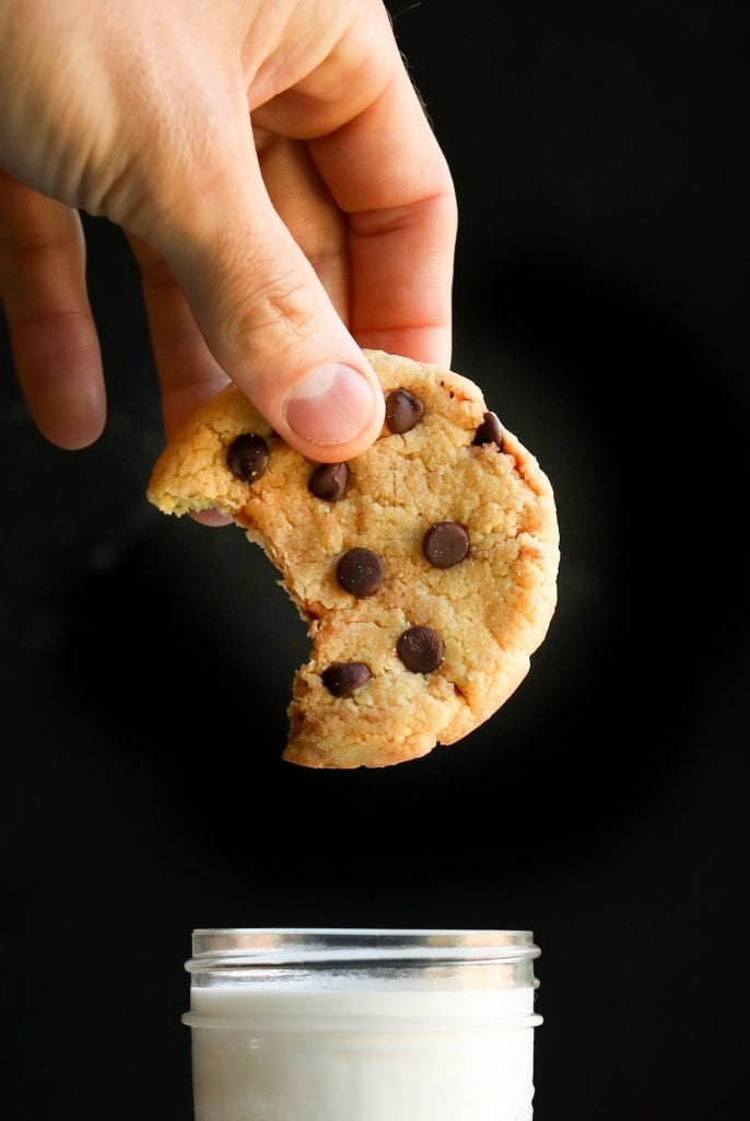 A chocolate chip cookie with a bite taken from it about to be dunked into a glass of milk.