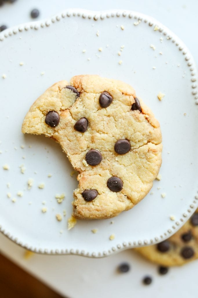 A chocolate chip cookie with a bite taken out of it laying on a plate.