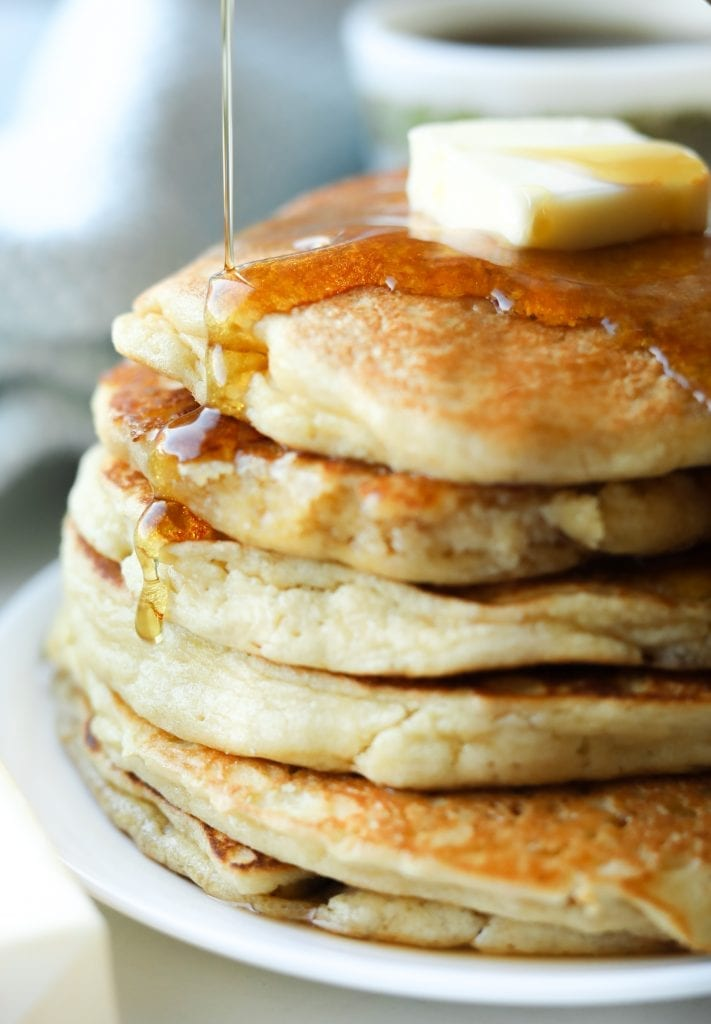 A stack of six pancakes laying on a plate with syrup running down the side of them.