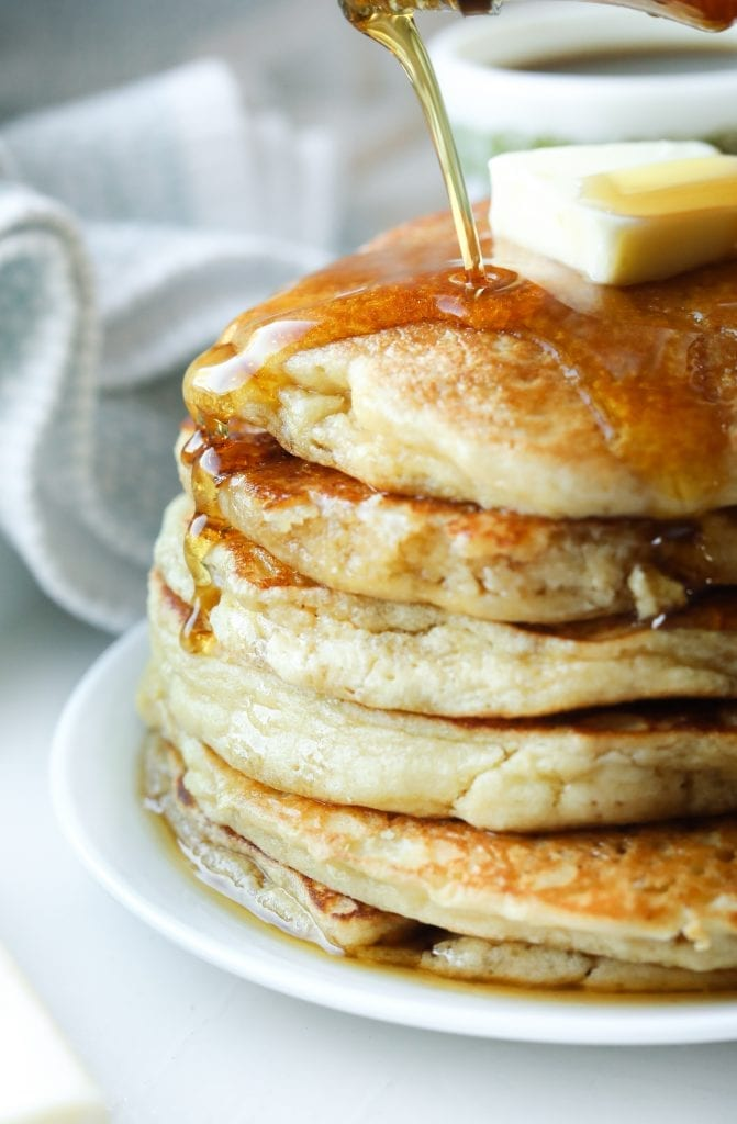 A stack of pancakes on a plate with syrup being poured on them.
