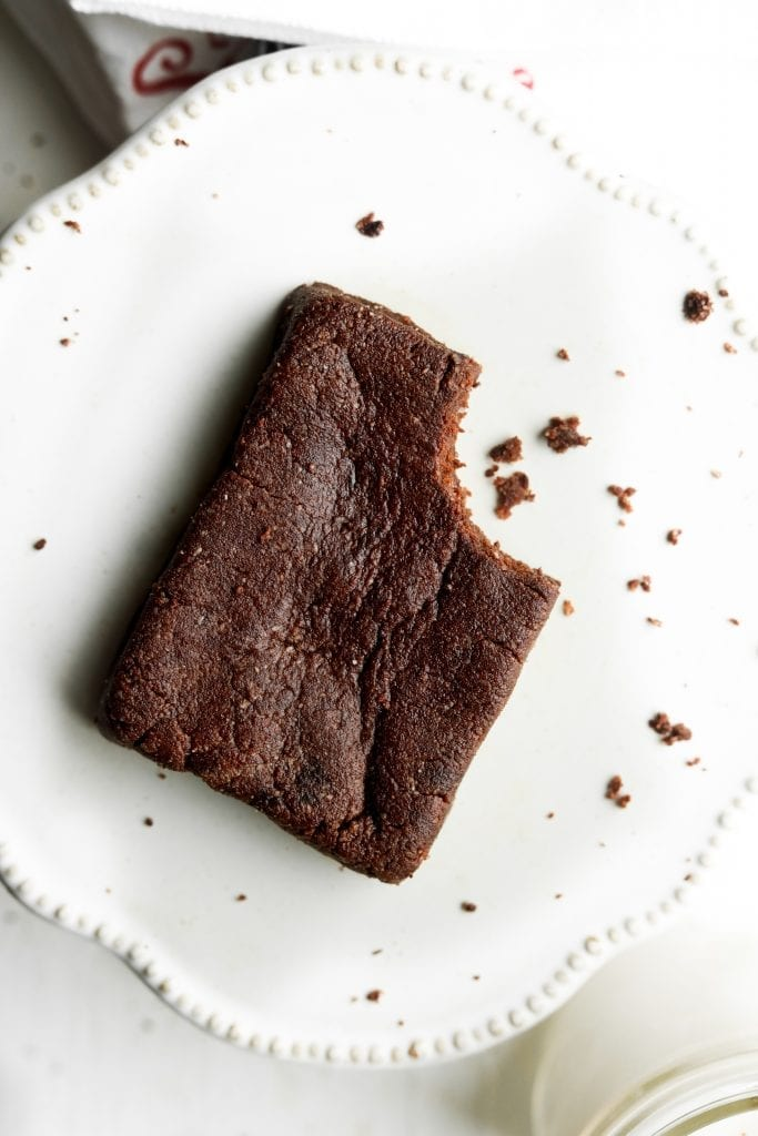 A brownie with a bite taken out of it sitting on a plate.