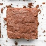 Keto brownies cut into square laying on parchment paper.