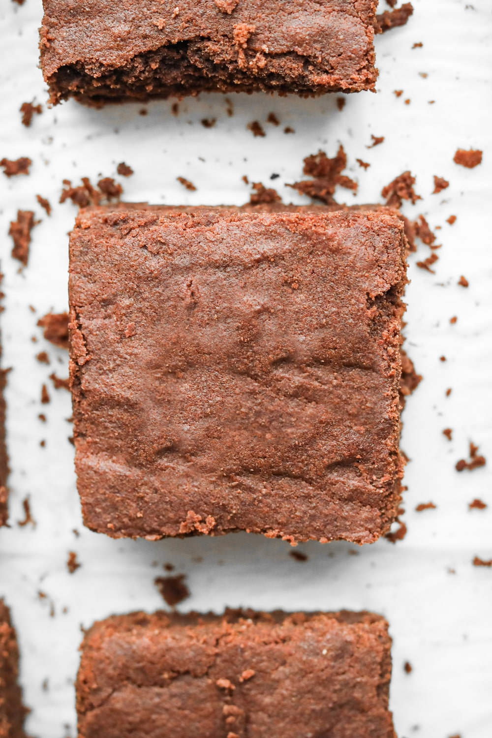 Keto brownies made with coconut flour cut into square laying on parchment paper.