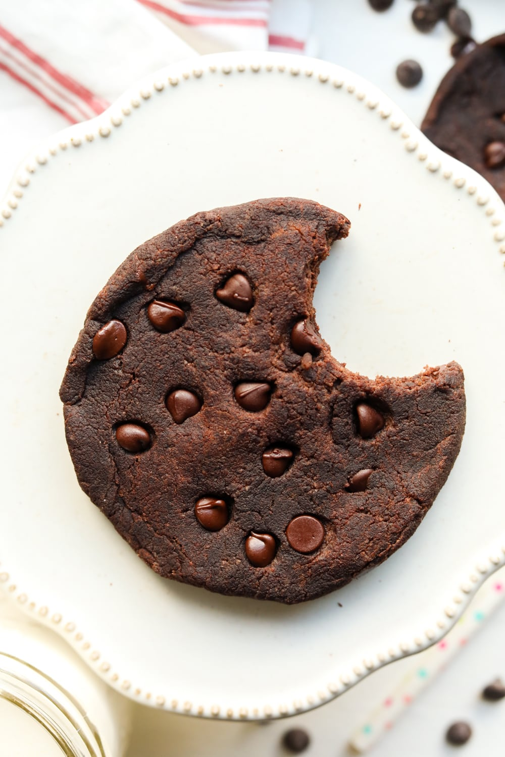 A double chocolate chip cookie with a bite taken out of it.