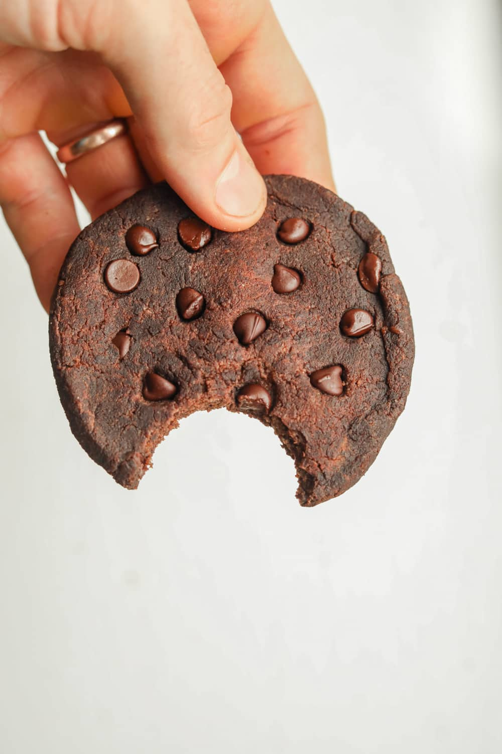 A double chocolate chip cookie that's been bitten being held in a hand.