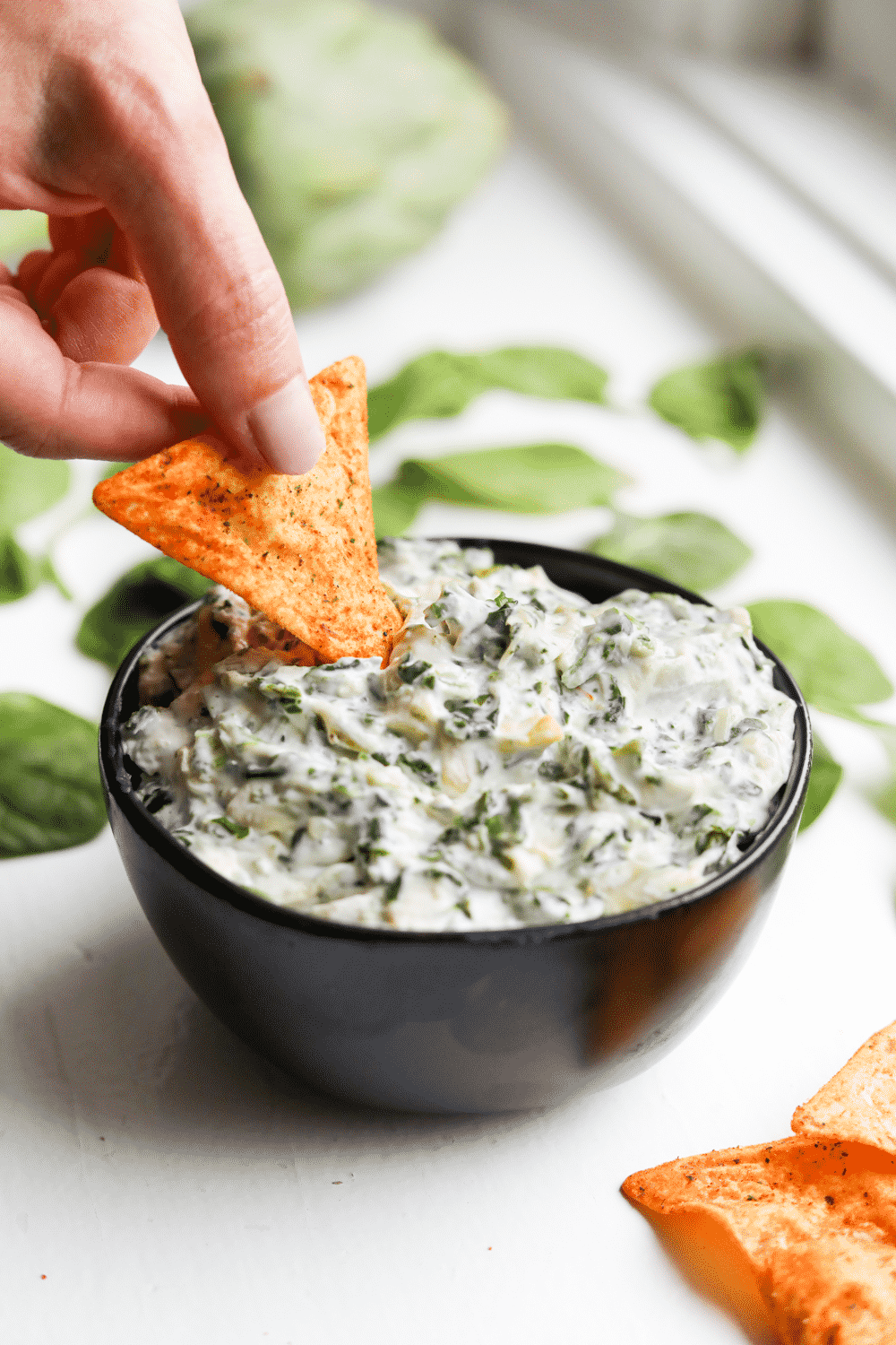 A chip about to be dunked it a bowl of keto dip