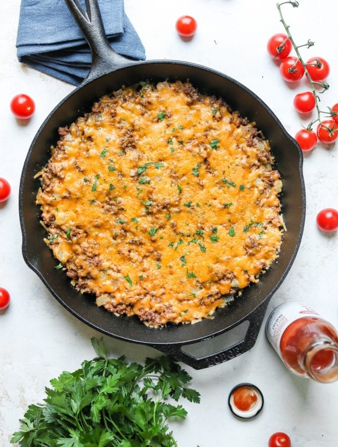 A keto cheeseburger casserole surrounded by tomatoes and low carb ketchup.