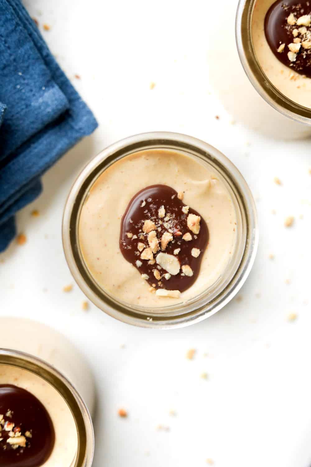 A jar of peanut butter keto mousse sitting on a table next to a napkin.