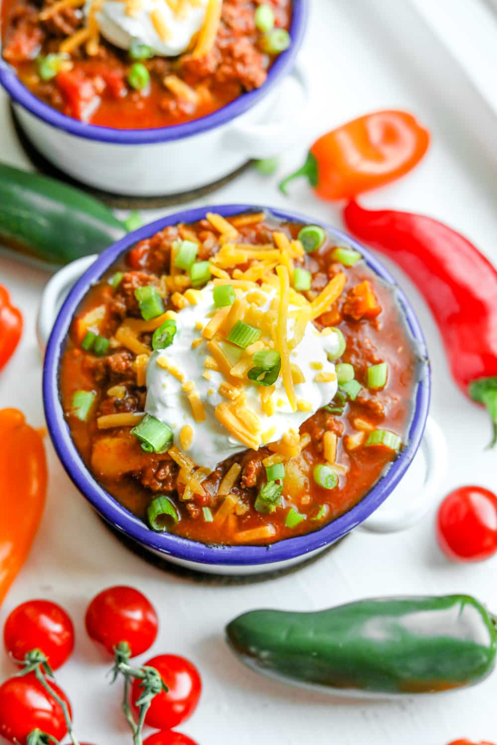 Low carb chili in a bowl topped with sour cream, cheese, and chives.