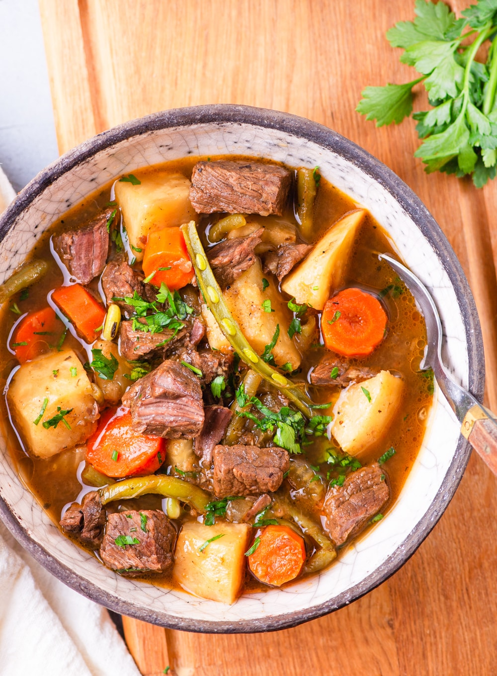 A bowl of beef stew with topped with fresh herbs.