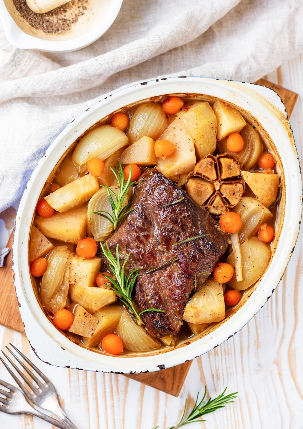 A pot roast surrounded by vegetables in a dutch oven.
