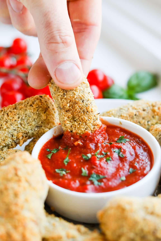 A hand dipping a mozzarella stick into marinara sauce.