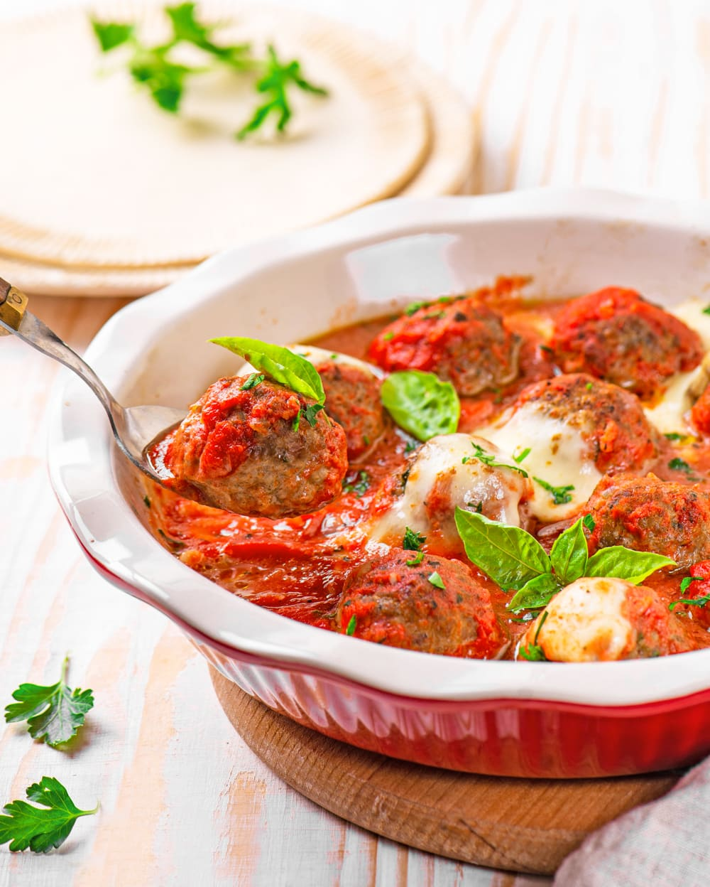 A spoon lifting a low carb meatball out of a pot.
