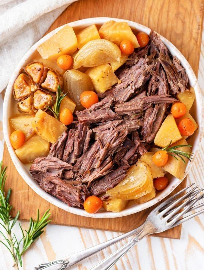 Keto pot roast on a serving platter next to a fork.