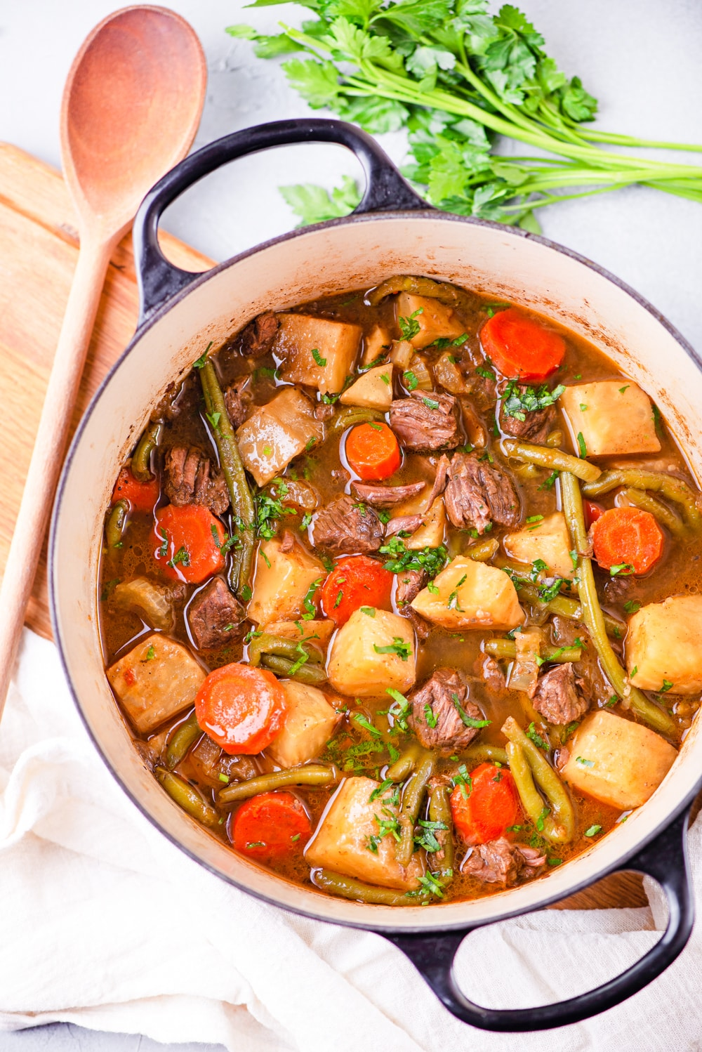 A pot with chunks of meat, carrots, and kohlrabi sitting in a broth, and topped with fresh herbs.