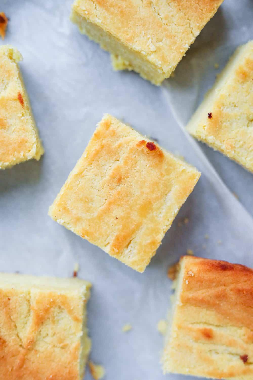 Keto cornbread cut up into slices on parchment paper.