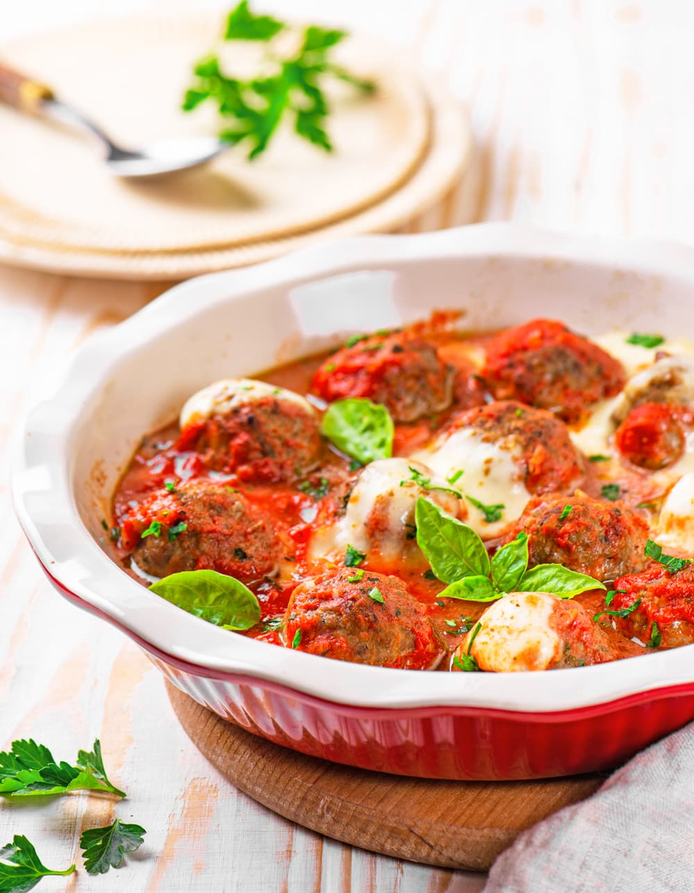 A ceramic bowl filled with low carb meatballs and tomato sauce.