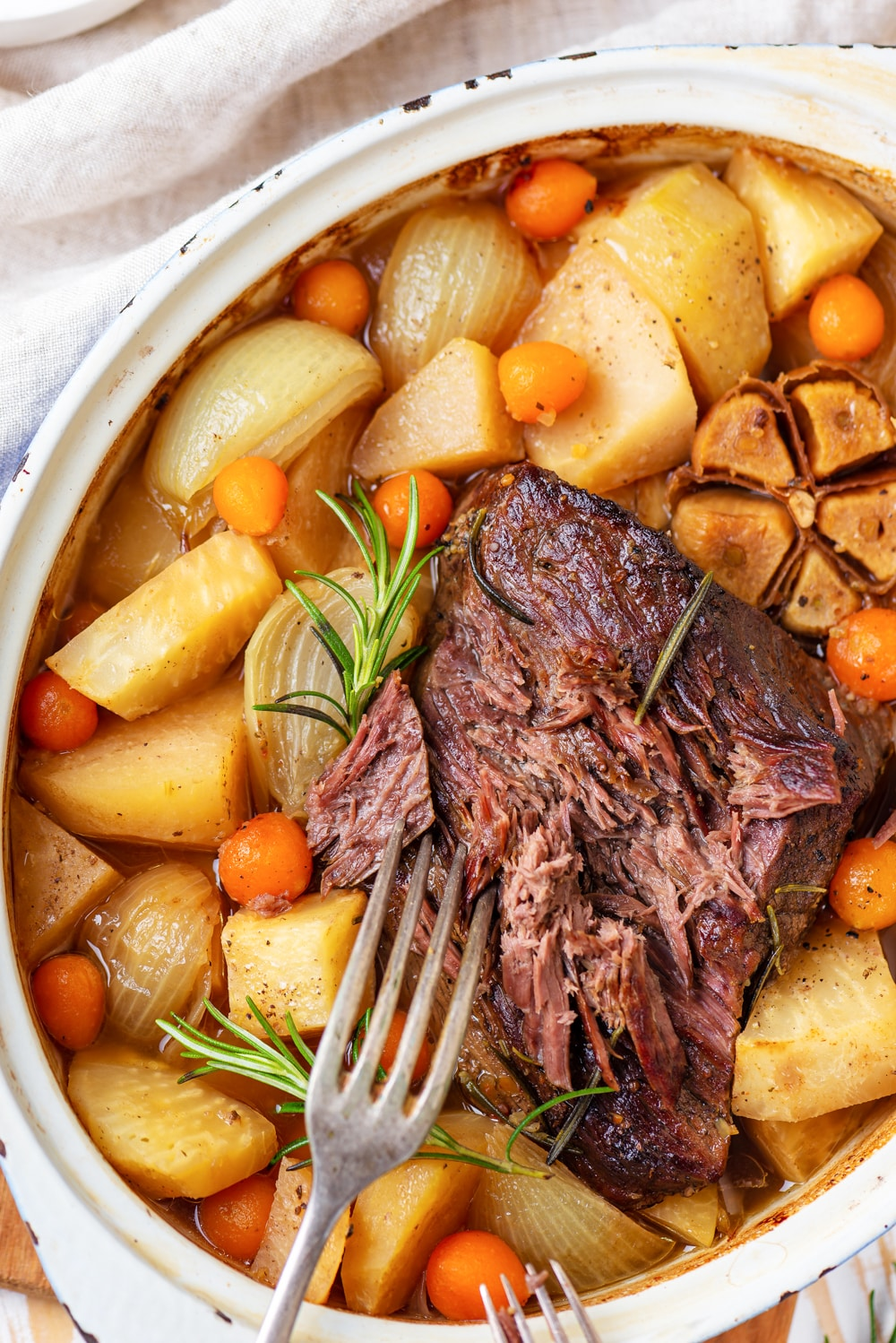A keto pot roast with a fork next to it surrounded by low carb vegetables.