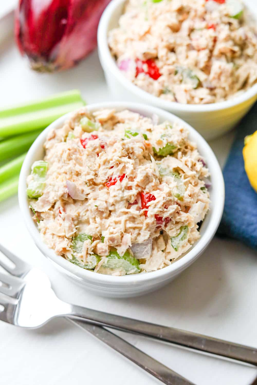 2 Bowls of tuna salad with and onion, lemon, celery, and forks next to them.