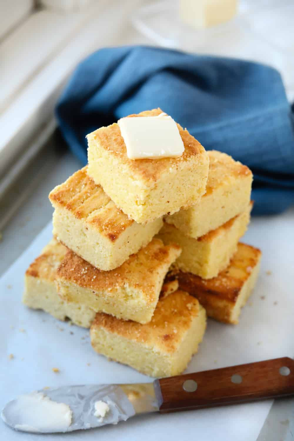 A baking sheet lined with parchment paper with slices of cornbread stacked on it.