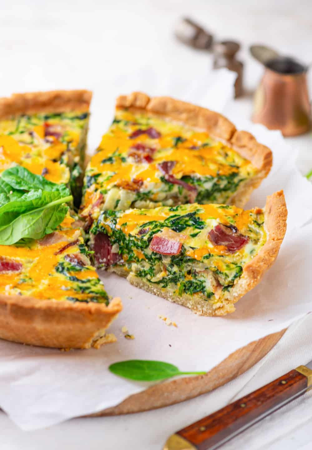 A slice of bacon and spinach quiche on parchment paper.