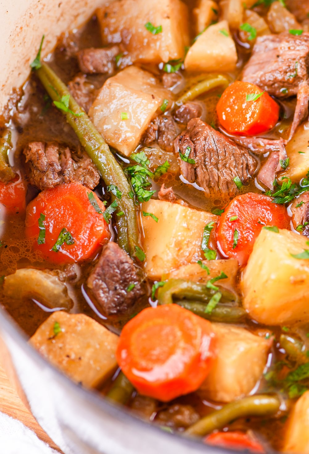 Chunks of beef, kohlrabi, and potatoes being cooked in a broth.