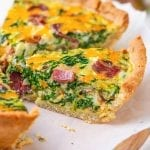 A slice of keto quiche filled with bacon and spinach set on top of parchment paper.