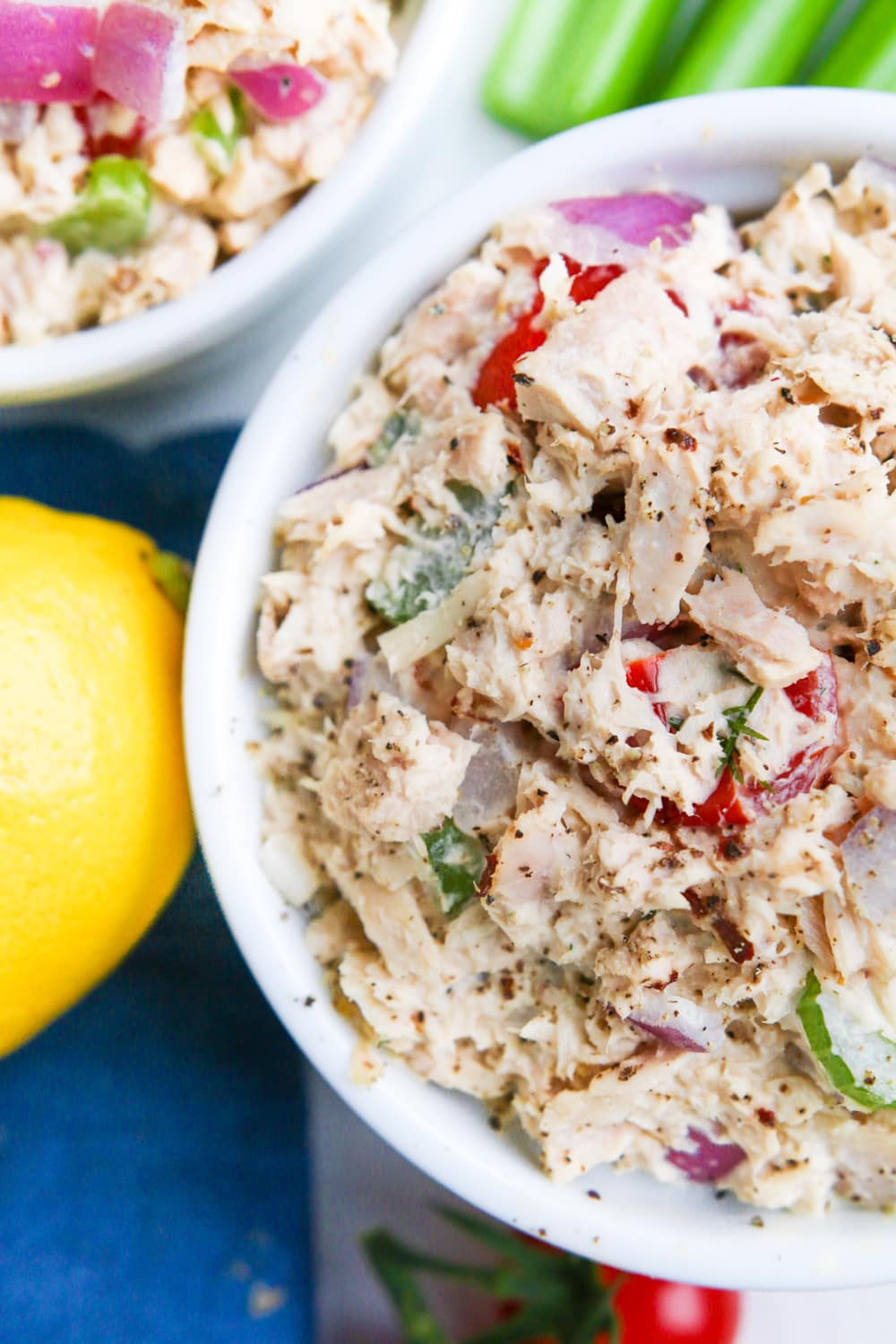 Two bowls of low carb tuna salad with a lemon, celery, and a blue napkin next to them.