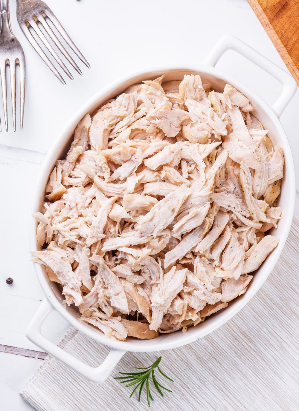 All white meat chicken shredded in a white casserole dish.