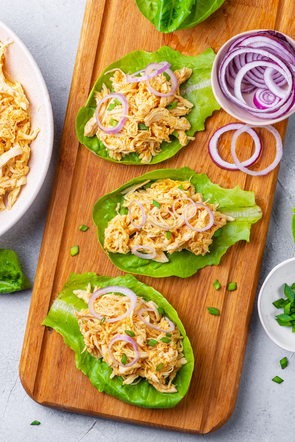 3 Shredded buffalo chicken lettuce wraps topped with green onions.