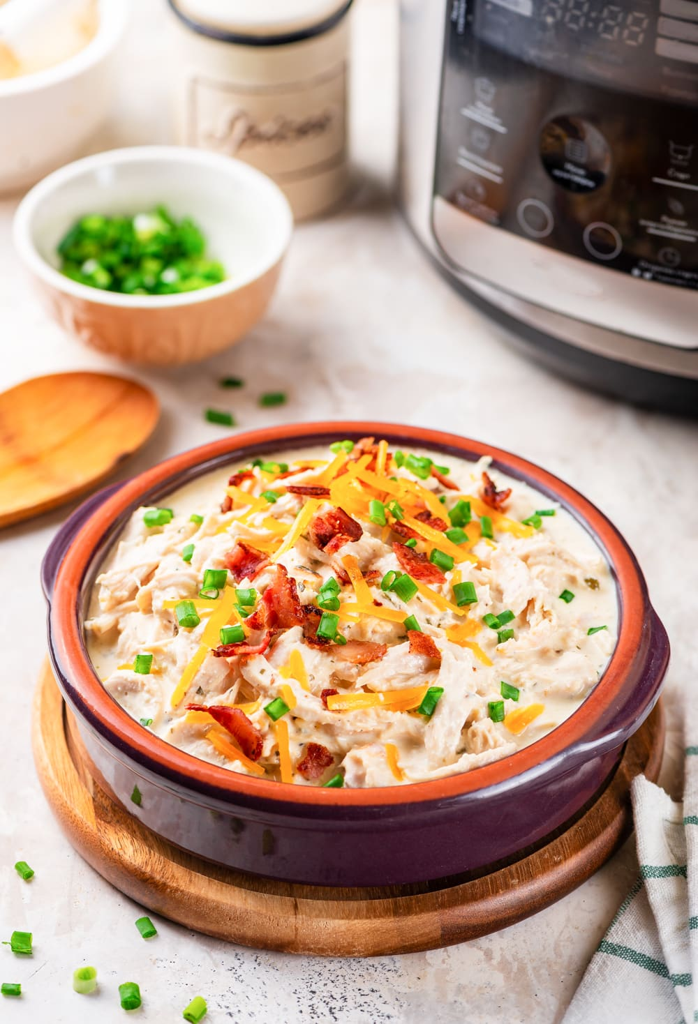 A bowl of keto crack chicken in front of an instant pot.
