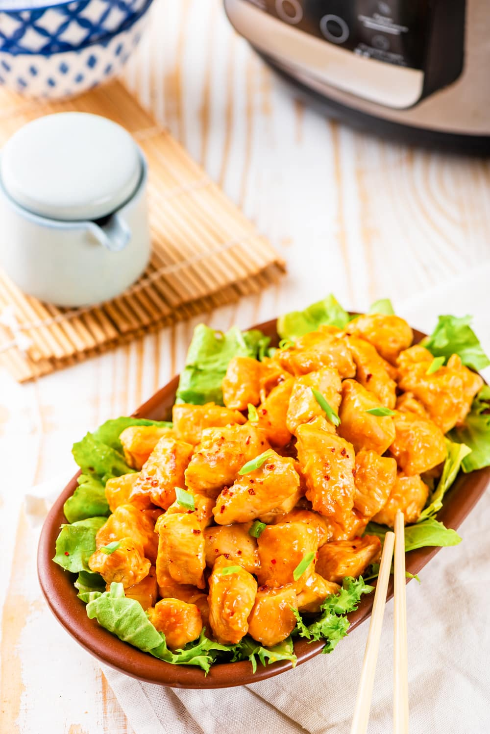 A brown bowl filled with lettuce and topped with orange chicken.