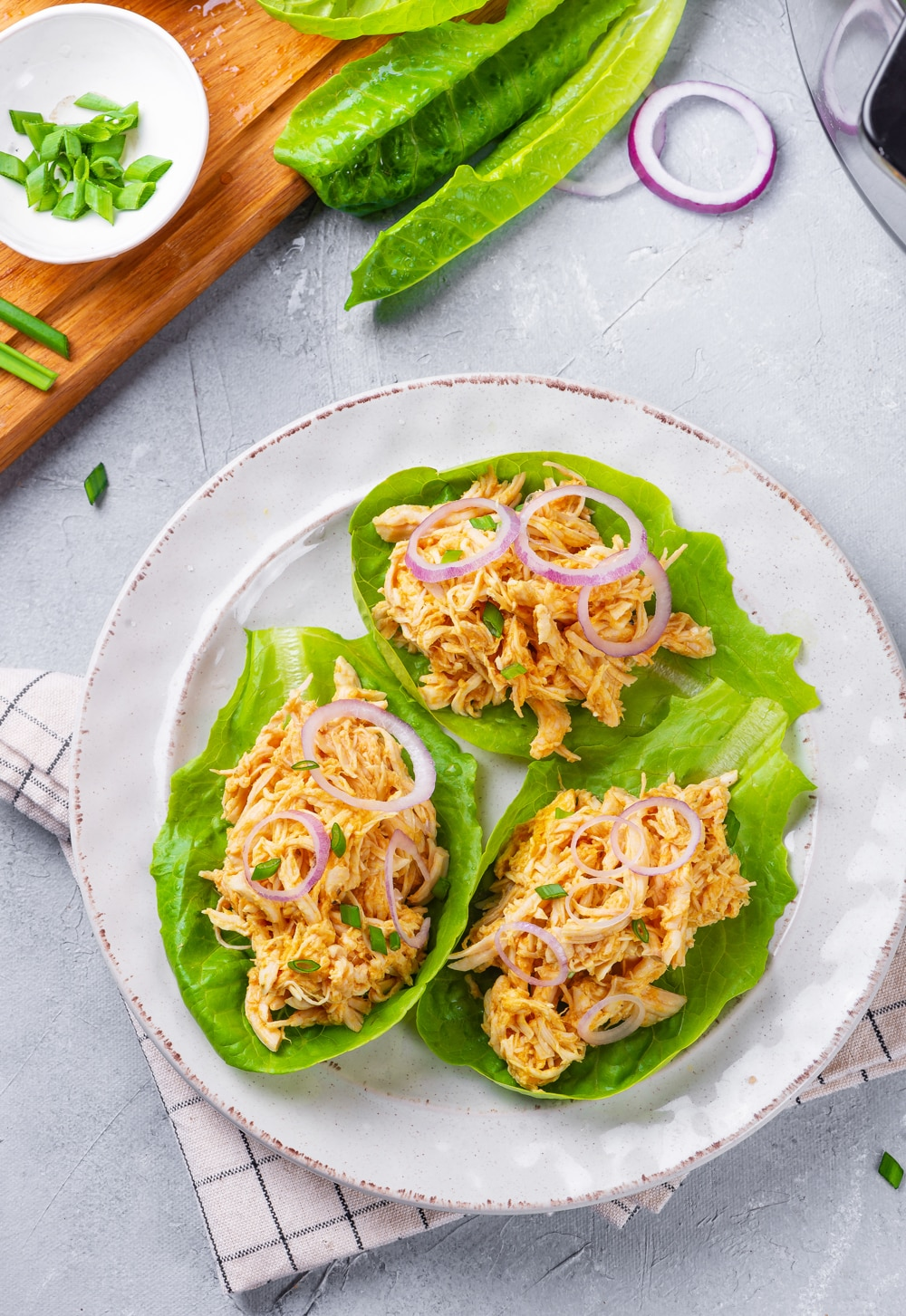 3 Buffalo chicken lettuce wraps topped with green and red onions on a white plate.