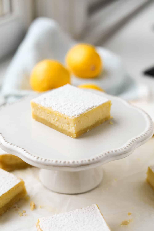 A lemon bar on a small serving dish.