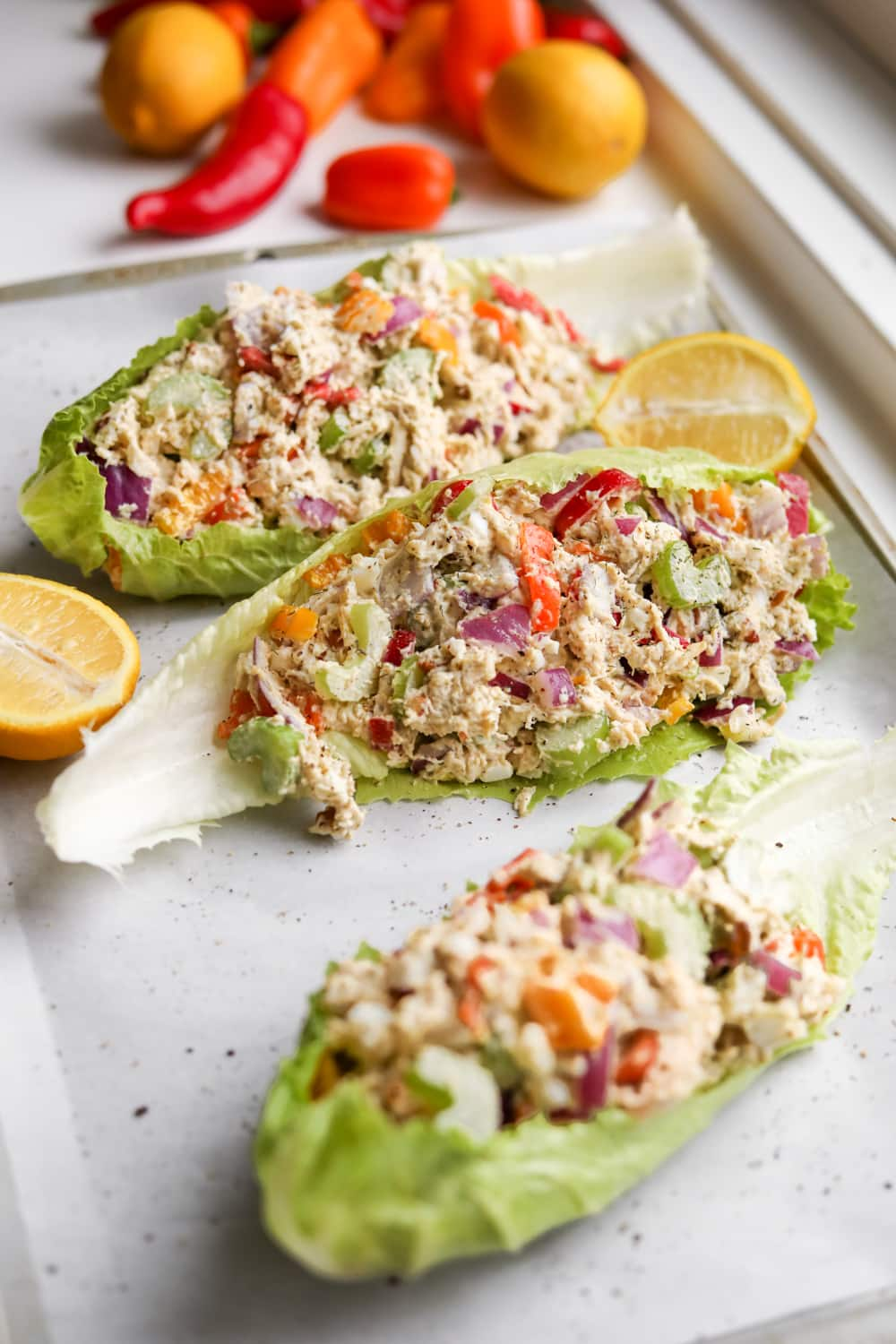 Lettuce wraps filled with chicken salad on a baking sheet.