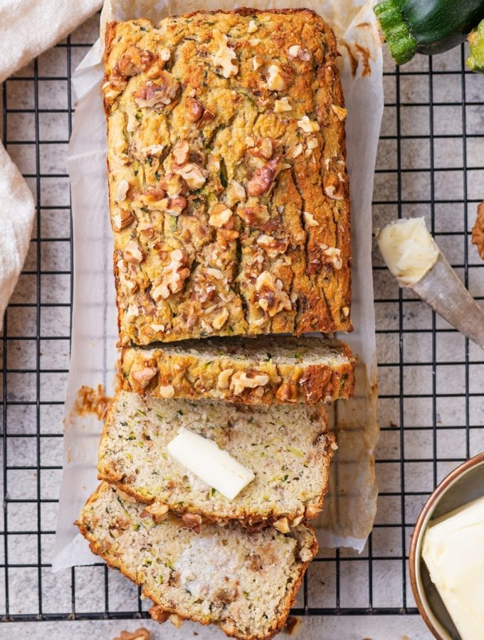 Zucchini bread with 3 slices cut from it and 2 of the slices covered with butter.