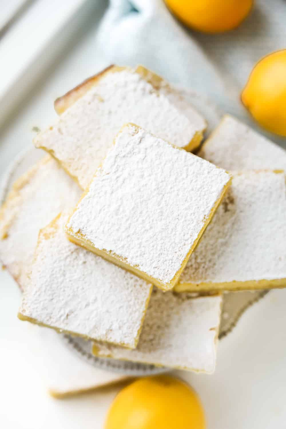 Keto lemon bars stacked on top of one another on a small cake plate.