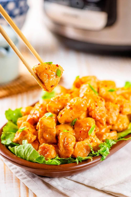 Chop sticks holding a piece of orange chicken with a bowl of orange chicken below it.