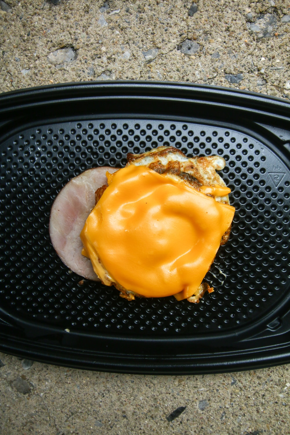 A slice of Canadian bacon topped with a rounded egg and cheese.