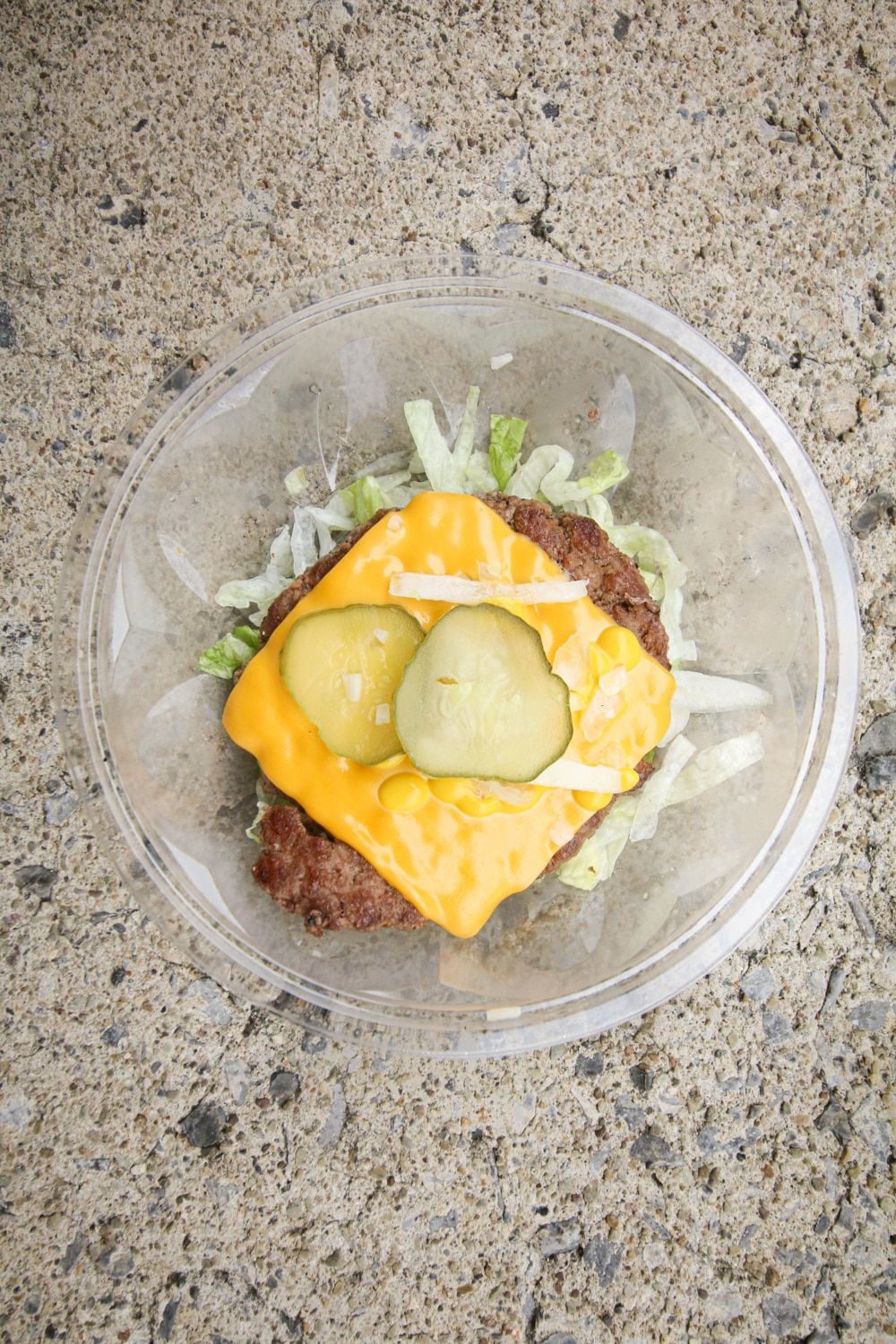 A ¼ pound beef patty on top of shredded lettuce and topped with cheese, sliced pickles, onions, and mustard.