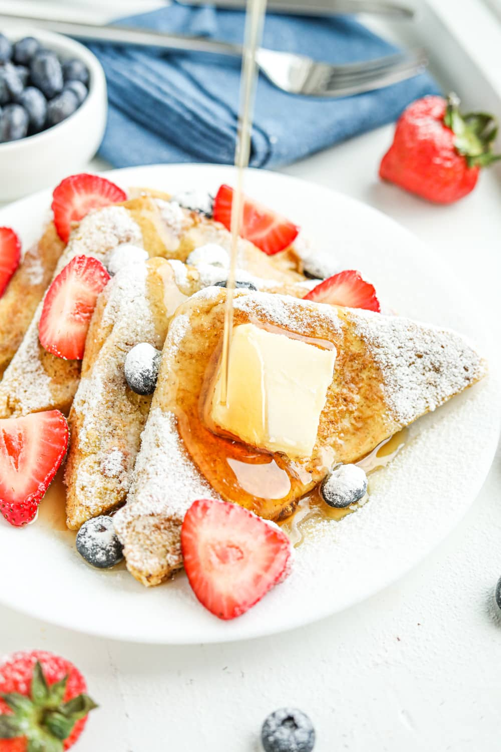 Syrup being drizzled on French toast and berries.