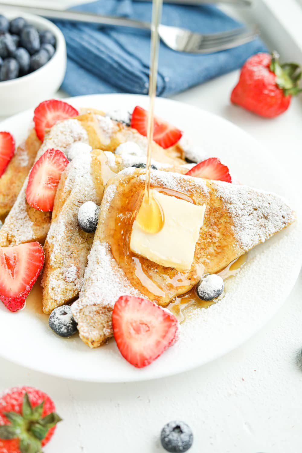 4 Slices of French toast on a white plate with syrup being poured on the toast.