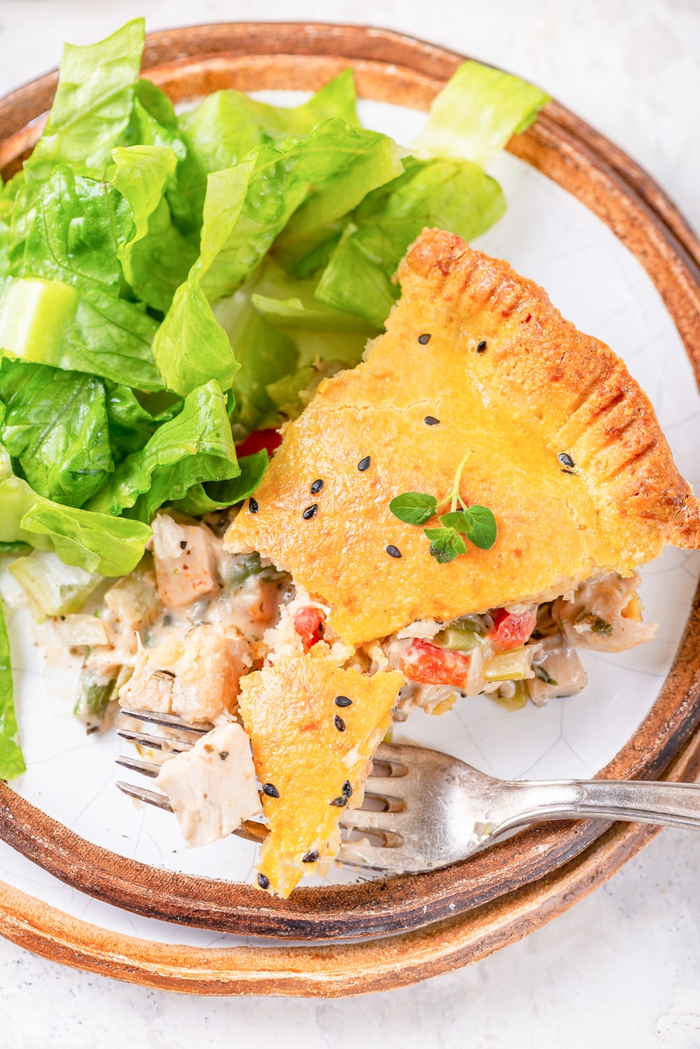 A slice of chicken pot pie on a plate with a salad next to it.