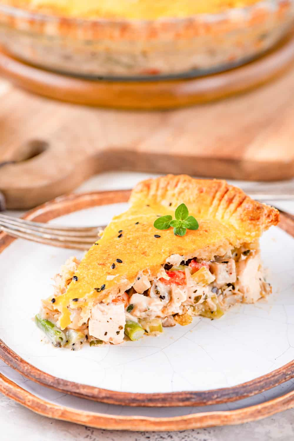 Chicken pot pie on a plate, and garnished with micro-greens.