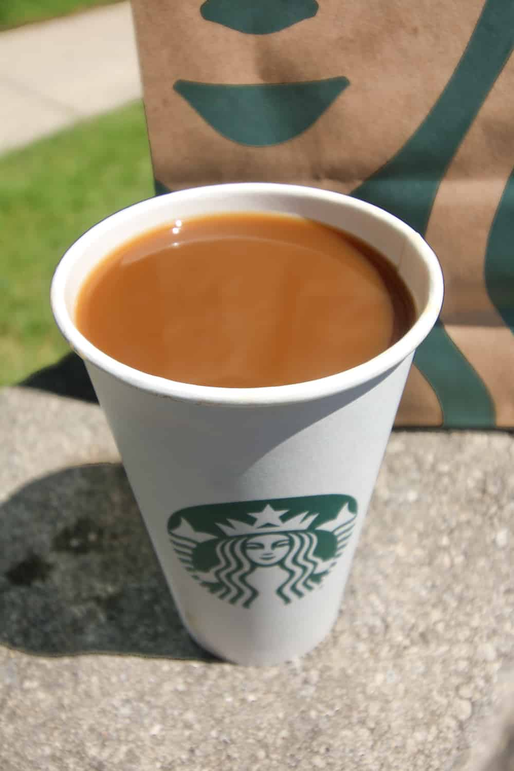 A hot coffee in a paper cup.